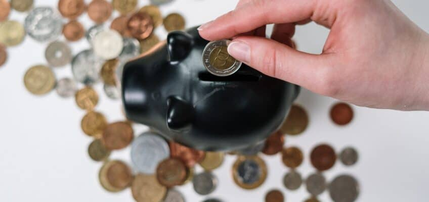 A hand introducing coins in a piggy bank
