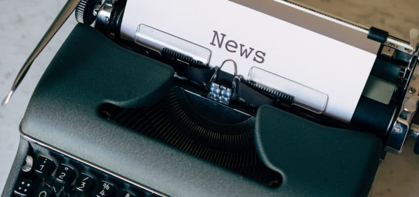 an old olympus typewriter with a paper that reads NEWS